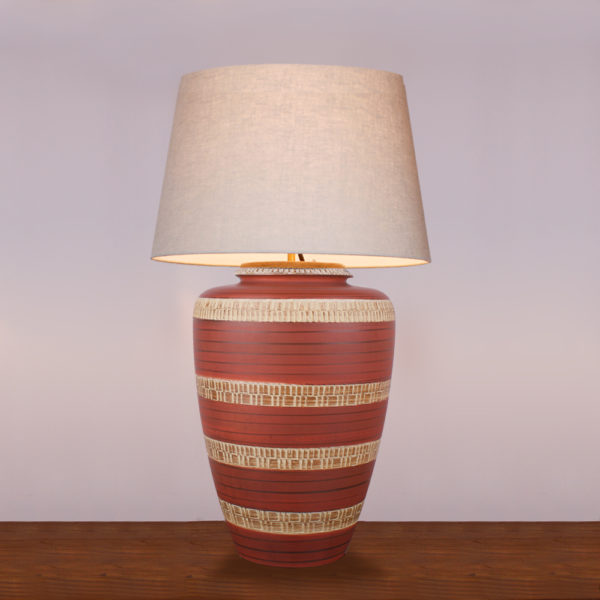 Die Tischlampe Bohemian in Terracotta Farbe hat eine warme Ausstrahlung. Die Farbe beruhigt und gibt dem Raum eine angenehme Atmosphäre. Der Lampenfuss besteht aus einer Vase aus den 1950er Jahren. Mittels einer Ritztechnik wurde in die Keramik ein geometrisches Muster in Ringen aufgebracht und anschließend wurde die Vase lasiert. Der Schirm und die Elektrik sind oben in den Hals der Vase eingesteckt und lassen sich bei Gebrauch der Vase abnehmen und auch als Blumenvase nutzen.