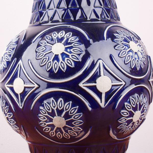 Die marineblaue und weisse Bodenvase steht auf einem Sockel der nach oben verlaufend in eine bauchige, fast kugelförmige Ausformung übergeht um darüber im gleichen Design in einen langen Vasenhals zur Öffnung übergeht. Die bauchige Ausformung besteht aus Romben mit einsetzten Kreisen und stilisierten Blumenblüten in weiss. Das Muster des Sockels und Halses ist in einer übereinanderliegenden Schuppentechnik in Dreiecksform gestaltet. Das Design stellt sich als Relief auf der Vase dar. Die Vase ist dunkelblau, glänzend lasiert und das Weiss der Keramik ist am Relief wie eine zweite Farbe zu sehen.