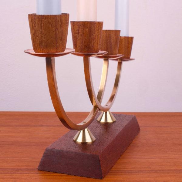 Dieser Kerzenleuchter ist aus den 1960er Jahren, der Mid Century Ära. Das Material ist aus Teakholz, Messing und Kupfer. Die Farben Braun, Gold und rosé wirken in der Einrichtung beruhigend und gemütlich. Die vier Kerzenhalter sind mit Tüllen aus Teak, Wachsauffangschalen aus Kupfer, einem Gestänge in einer Art Kreuzform aus Messing und einem Sockel aus Teak, der sich trapezförmig zu den Seiten verbreitert, gefertigt. Durch die Kaskadenanordnung der Kerzenhalter stehen die Kerzen treppenartig nebeneinander. Das Design ist im mid century modern Style gestaltet.