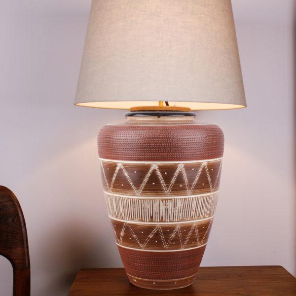 Die Tischlampe Boho Style Braun Creme hat eine warme Ausstrahlung. Die Farbe beruhigt und gibt dem Raum eine angenehme Atmosphäre. Der Lampenfuss besteht aus einer Vase aus den 1950er Jahren. Mittels einer Ritztechnik wurde in die Keramik ein geometrisches Muster in Ringen und senkrechten Linien aufgebracht und anschließend wurde die Vase teilweise mit weisser Farbe lasiert und gebrannt. Der oberer Rand der Vase ist mit einem kleinen Kragen in dunkelbraun gestaltet. Der Schirm und die Elektrik sind oben in den Hals der Vase eingesteckt und lassen sich bei Gebrauch der Vase abnehmen und auch als Blumenvase nutzen. Diese Lampe ist ein Unikat.