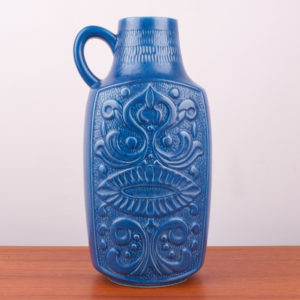 Die Bodenvase ist aus Keramik und ist in einem komplett azurblau seidenmatt lasiert. Sie ist mit einem Henkel versehen, der oben am Hals seitlich angesetzt ist. Fast wie ein Krug. Nur ohne Ausguss. Der Hals der Bodenvase ist durchgehend rund. Die Oberflächengestaltung ist an die Zeit der Inkas angelehnt. Das Dekor sieht fast wie ein Gesicht in Form eines Blumenornaments aus und liegt erhaben auf der Oberfläche wie ein Relief. Oben am Hals befindet sich ein Ritzdekor von aneinandergesetzten vertikalen Linien, die um den Hals der Vase gezeichnet wurden. Wer auf die Mid Century Ära steht, wird diese Vase gern in seinem zu Hause haben wollen. Auf der Vase ist noch ein Teil des Originalaufklebers erhalten. Der kann natürlich entfernt werden.