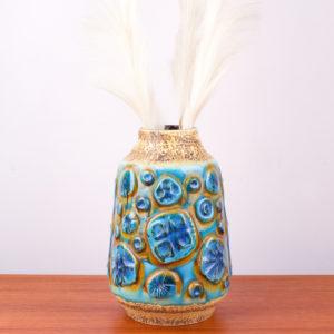 Diese Vase hat so erfrischende Farbkomponenten, dass man gleich an Meer, Sand und Himmel denken muss. Sie läuft konisch, von unten breit zum Hals schmal zu. Der Hals der Vase setzt sich vom Korpus durch einen Schwung nach oben ab. Das wilde Dekor auf der Vase erinnert an ein archaisches Muster, oder auch an stilisierte Blütenstände. Oder auch an Versteinerungen. Die sandfarbene Oberfläche der Vase ist unregelmäßig, rauh und die blauen und türkis lasierten Flächen sind hochglänzend gestaltet. Die Oberfläche wechselt sich somit sehr interessant ab. In der Mid Century Ära wurde in der Gestaltung das archaische Thema gern interpretiert. Der türkisfarbene Ton erinnert an karibisches Meer. Die sandfarbene Oberfläche ist wie Sand am Meer. Diese Vase ist ein echtes Statement und braucht zum Ausgleich zum Beispiel einen Teakholztisch. In die Vase passen ganz wunderbar Pampasgras, oder hochstilige Blumen.