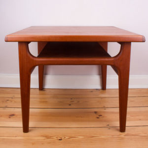 Der Designer Niels Bach hat für die Möbelmanufaktur Randers in den 1970er Jahren gestaltet. Der quadratische coffee table ist ein Designstück aus den 70er Jahren ist super praktisch für die kleine Wohnung. Der Tisch kann aber auch für ein großes Ecksofa, oder eine Wohnlandschaft genutzt werden. Der Tisch ist aus massivem Teakholz gefertigt. Eine unter der Hauptplatte angebrachte Zwischenplatte dient als praktische Zeitungsablage. Die Zwischenablage hat etwa eine Höhe von 10cm. Die Tischbeine ziehen sich in einer konisch verlaufenden Form von unten schmal nach oben etwas breiter werdend zu der unteren Platte. Auf den vier einsehbaren Seiten sind die Ecken zwischen den Beinen auf zwei Seiten abgerundet und auf den zwei anderen Seiten werden die Tischbeine durch jeweils eine Querstrebe gehalten und verstärkt.